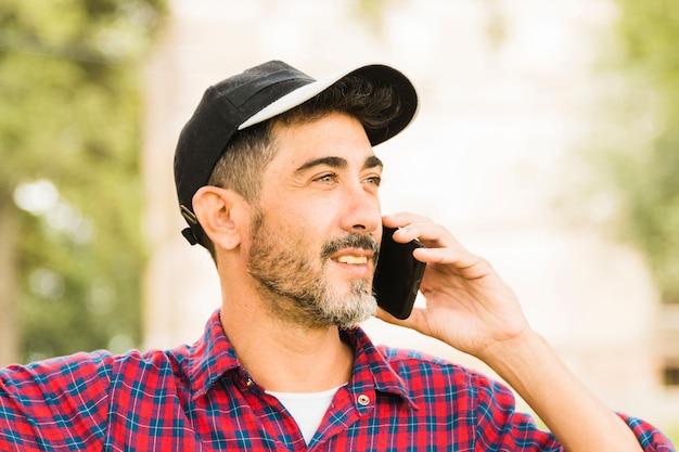 Homme élégant portant un bonnet noir sur la tête parlant au téléphone mobile Photo gratuit