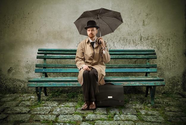 Homme élégant triste assis avec un parapluie Photo Premium