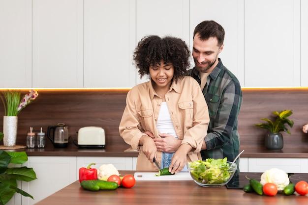 Homme embrassant une belle femme en train de cuisiner Photo gratuit