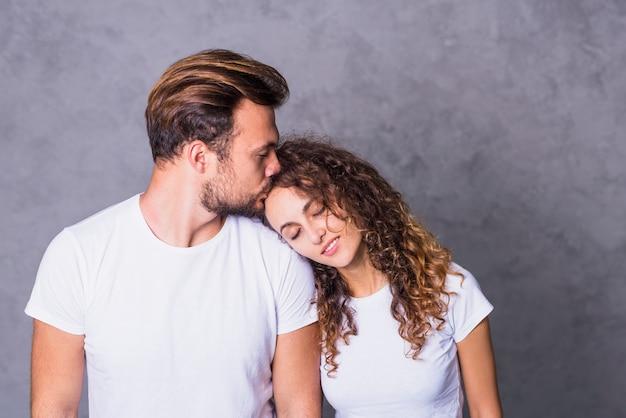 Homme embrassant une femme sur le front Photo gratuit