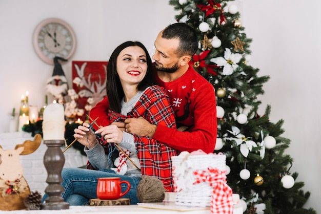 Homme embrassant femme tricotant près de sapin de noël Photo gratuit