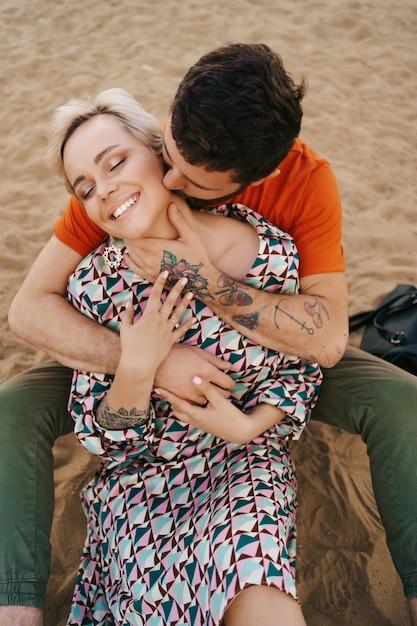 Homme Embrassant Tendrement Le Cou De Sa Femme L'étreignant Avec Des Mains Magnifiquement Tatouées Tout En Vous Relaxant Sur Le Sable Photo gratuit