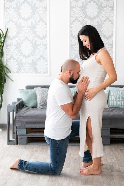 Homme embrassant le ventre de sa femme Photo gratuit
