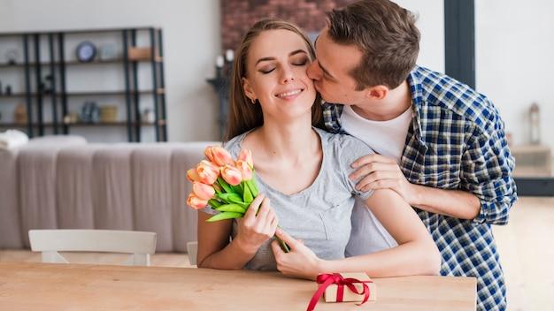 Homme embrasse une femme heureuse et donne des cadeaux Photo gratuit
