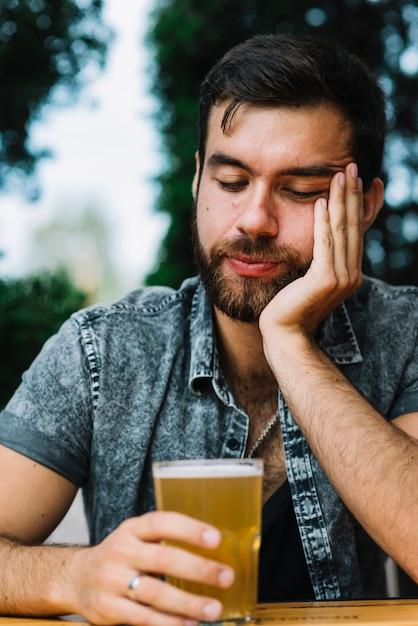 Homme endormi tenant un verre de bière Photo gratuit