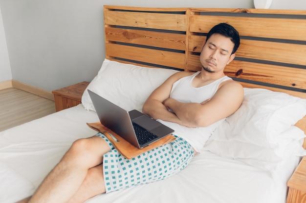 Homme endormi travaille avec son ordinateur portable sur son lit douillet. concept de style de vie ennuyeux pigiste. Photo Premium