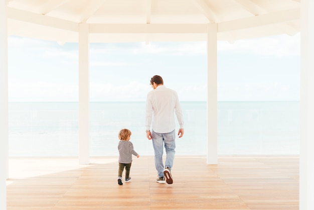 Homme et enfant en bas âge marchant sur le porche Photo gratuit