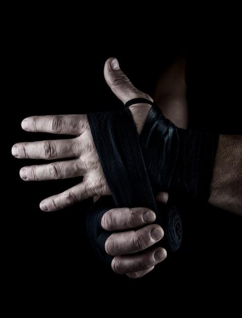 Un homme enveloppe ses mains dans un bandage textile noir pour le sport Photo Premium
