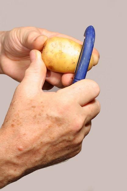 Homme épluche des pommes de terre Photo Premium