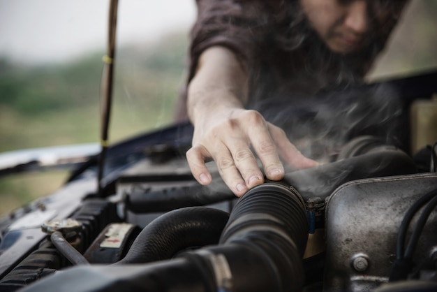 Homme essayant de réparer un problème de moteur de voiture sur une route locale Photo gratuit