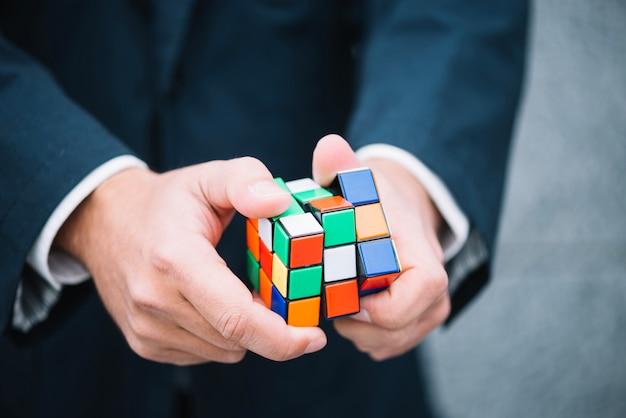 Homme essayant de résoudre le cube de rubik Photo gratuit