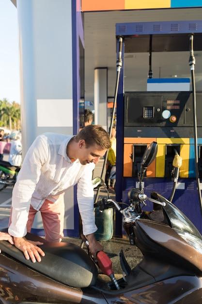 Homme, essence, moto, sur, station, moto, essence, vélo Photo Premium
