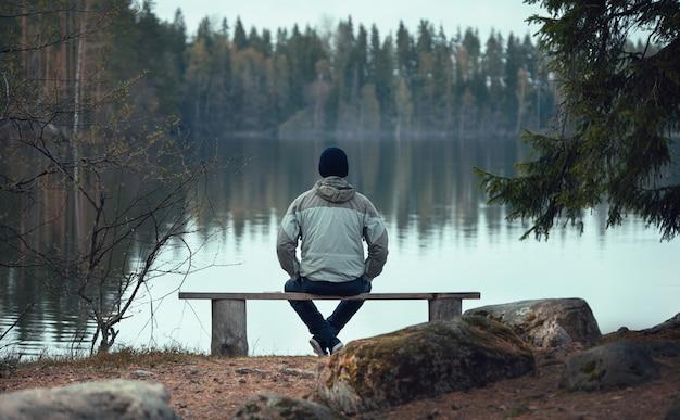 Un Homme Est Assis Sur Un Banc Près D'un Lac De La Forêt. Vue De L'arrière. Photo Premium