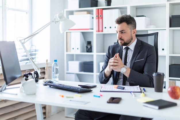 Un Homme Est Assis Sur Une Chaise Dans Le Bureau à La Table Et Regarde L'écran. Photo Premium
