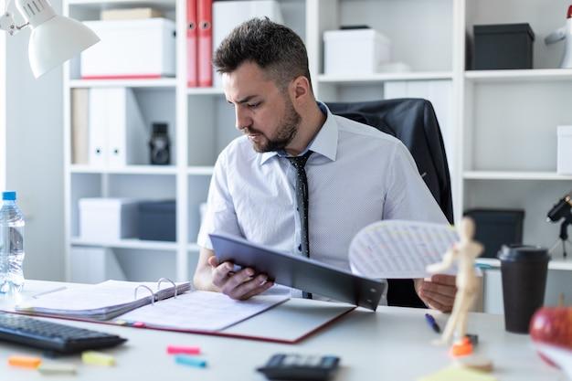 Un homme est assis dans le bureau et fait défiler les documents. Photo Premium