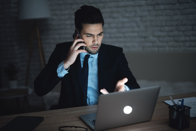 Un homme est assis devant un ordinateur portable dans un bureau sombre. Photo Premium