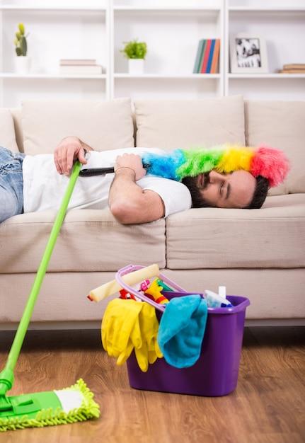 L'homme est fatigué et dort sur le canapé pendant le nettoyage à la maison. Photo Premium
