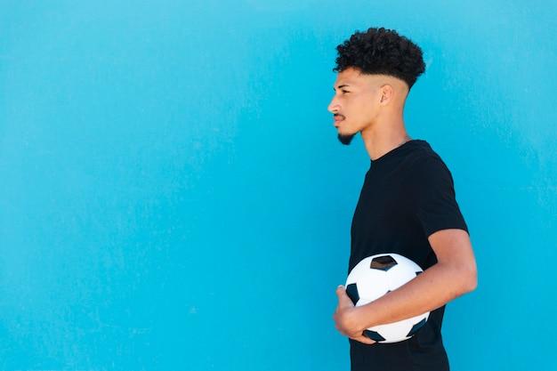 Homme ethnique aux cheveux bouclés debout avec le football Photo gratuit