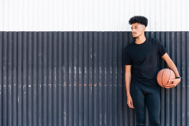 Homme ethnique avec basket regardant loin Photo gratuit