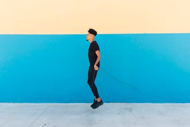 Homme ethnique, corde à sauter dans la rue Photo gratuit
