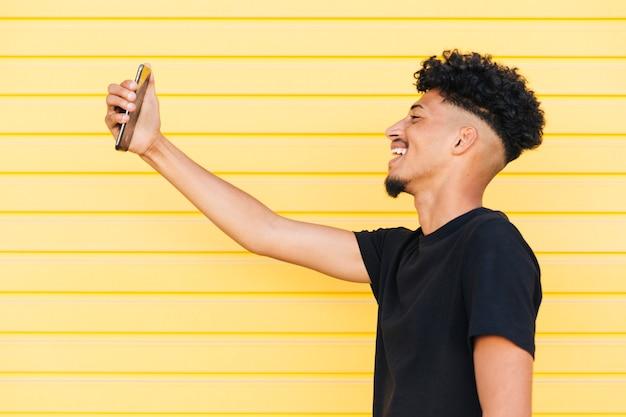 Homme ethnique souriant prenant selfie Photo gratuit