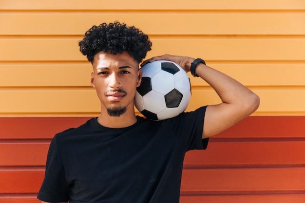 Homme ethnique tenant un ballon de foot sur l'épaule Photo gratuit