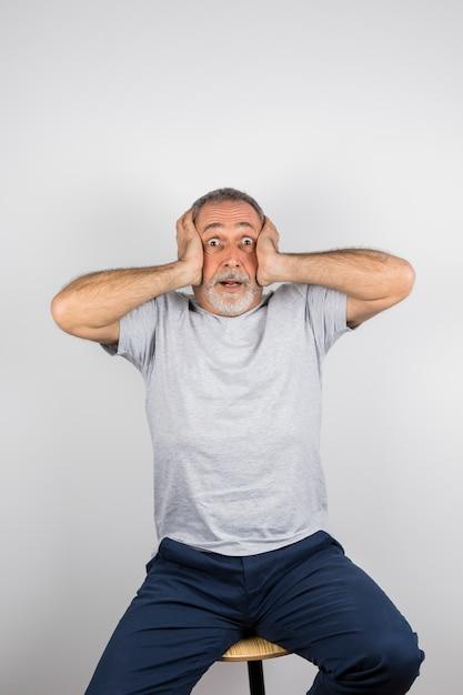 Homme étonné âgé avec les mains sur la tête sur une chaise Photo gratuit
