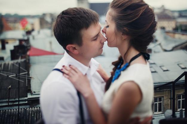 L'homme étreint une jolie femme tendue et l'embrasse sur le toit Photo gratuit
