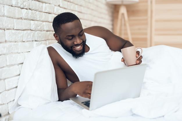 Homme éveillé noir boit du café au lit tout en travaillant Photo Premium
