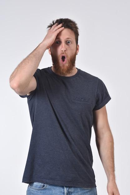 Homme avec expression d'oubli ou de surprise sur blanc Photo Premium