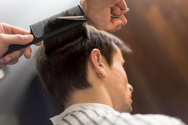 Homme à faible angle se faire couper les cheveux Photo gratuit