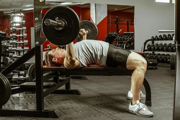 Homme faisant de l'exercice dans la salle de sport locale Photo Premium
