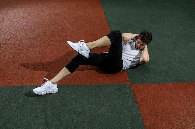 Homme Faisant Des Exercices De Torsion Abs Avec Les Jambes Levées. Photo D'un Jeune Homme En Plein Air Dans La Ville Photo Premium