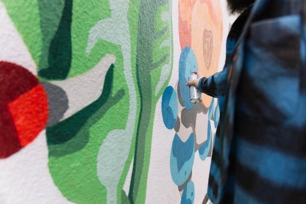Homme faisant des graffitis avec aérosol sur le mur Photo gratuit