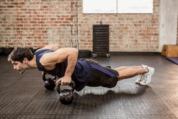 Homme faisant des push ups avec kettlebell Photo Premium