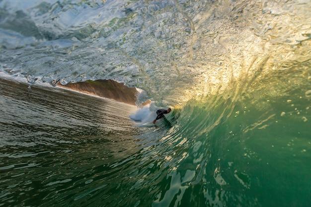 Homme Faisant Des Tours De Surfeur Prenant En Charge Les Fortes Vagues De L'océan En Algarve, Portugal Photo gratuit