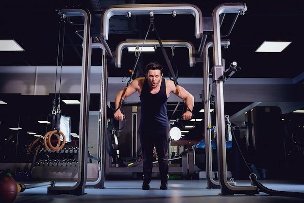 Un homme fait des exercices sur simulateur dans le gymnase Photo Premium