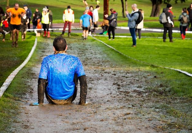 Un homme fatigué, épuisé après une activité physique extrême, dans une course de boue Photo Premium
