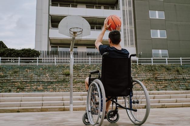 Un homme en fauteuil roulant joue au basket Photo Premium
