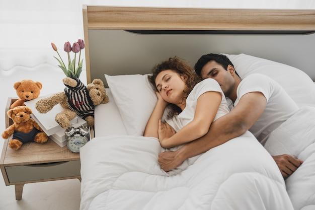 Un homme et une femme allongés sur un lit Photo Premium