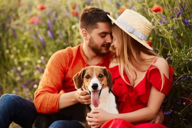 Homme et femme assis avec un drôle beagle sur le champ vert avec des coquelicots rouges Photo gratuit