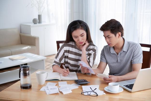 Homme et femme calculant le budget domestique à la maison Photo gratuit