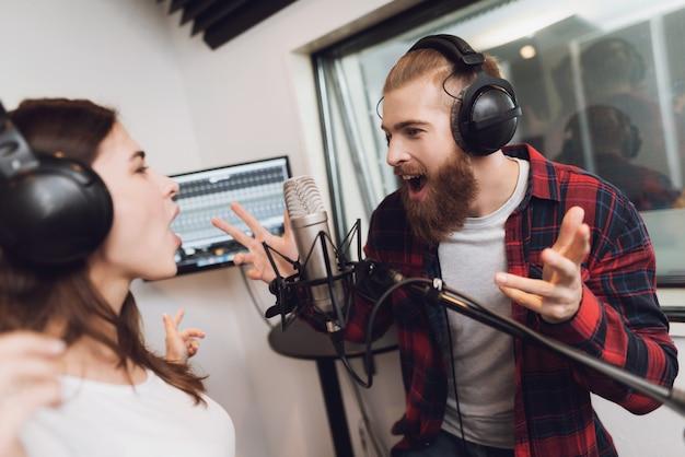 Un Homme Et Une Femme Chantent Une Chanson Dans Un Studio D'enregistrement Moderne Photo Premium