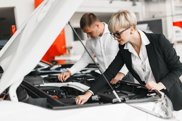 Un homme et une femme choisissent une voiture chez un concessionnaire et regardent sous le capot d'une voiture. Photo Premium
