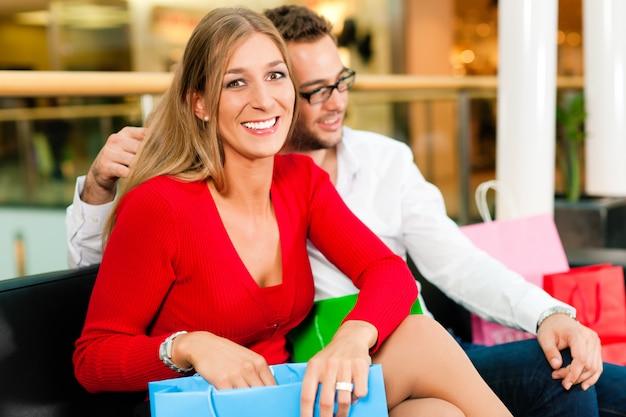 Homme et femme dans un centre commercial avec des sacs Photo Premium