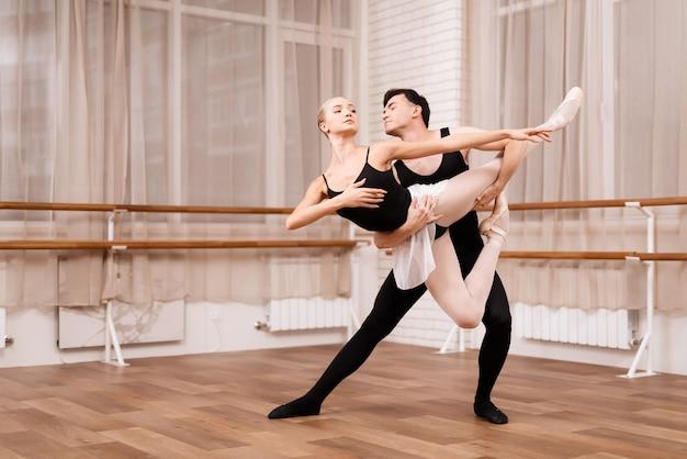 Homme et femme danseurs posant en classe de ballet. Photo Premium