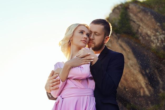 Homme et femme étreignant en été au coucher du soleil dans de beaux vêtements. couple amoureux Photo Premium