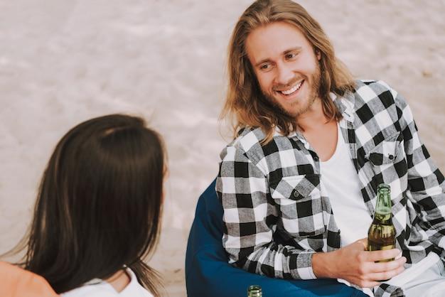 Homme et femme heureux hipster parlent à la fête sur la plage Photo Premium