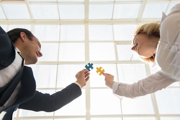Homme et femme joignant des morceaux de puzzle au bureau. Photo Premium