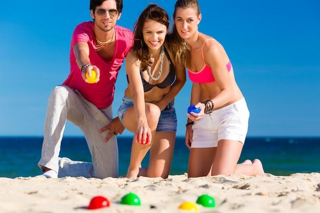 Homme et femme jouant à la boule sur la plage Photo Premium
